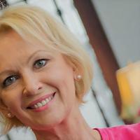 Smiling blonde woman wearing a pink shirt