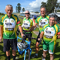 Vision impaired man on left stands with a group of cyclists, all dressed in green and gold