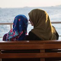 Two women wearing head scarves talking on a seat in front of the ocean